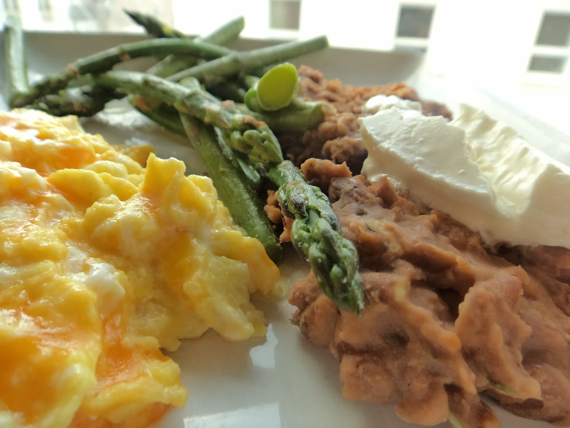 Cheesy scrambled eggs, asparagus and refried beans.
